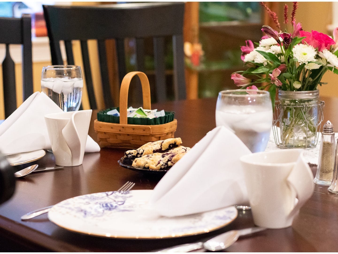 A cup of coffee and a vase of flowers on a table at Hammer Creek Hideaway Bed & Breakfast.