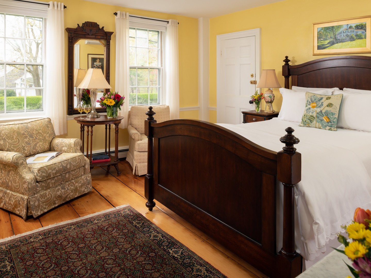 A living room filled with furniture and a large window at Candleberry Inn on Cape Cod.