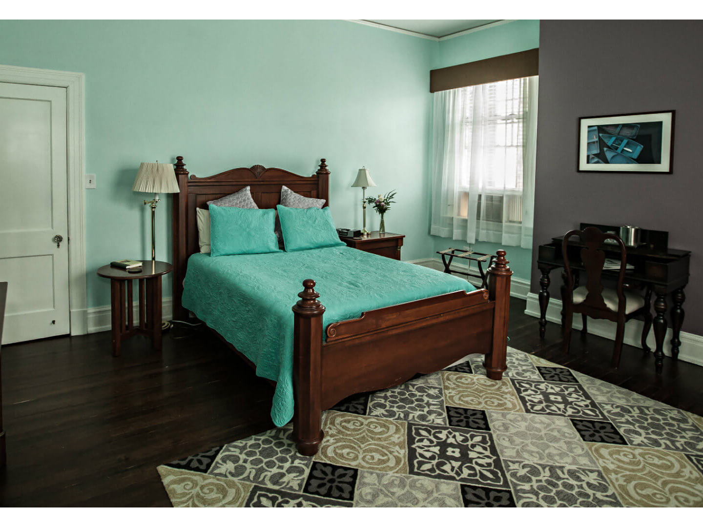 A bedroom with a bed and a chair in a room at Morehead Manor Bed and Breakfast.