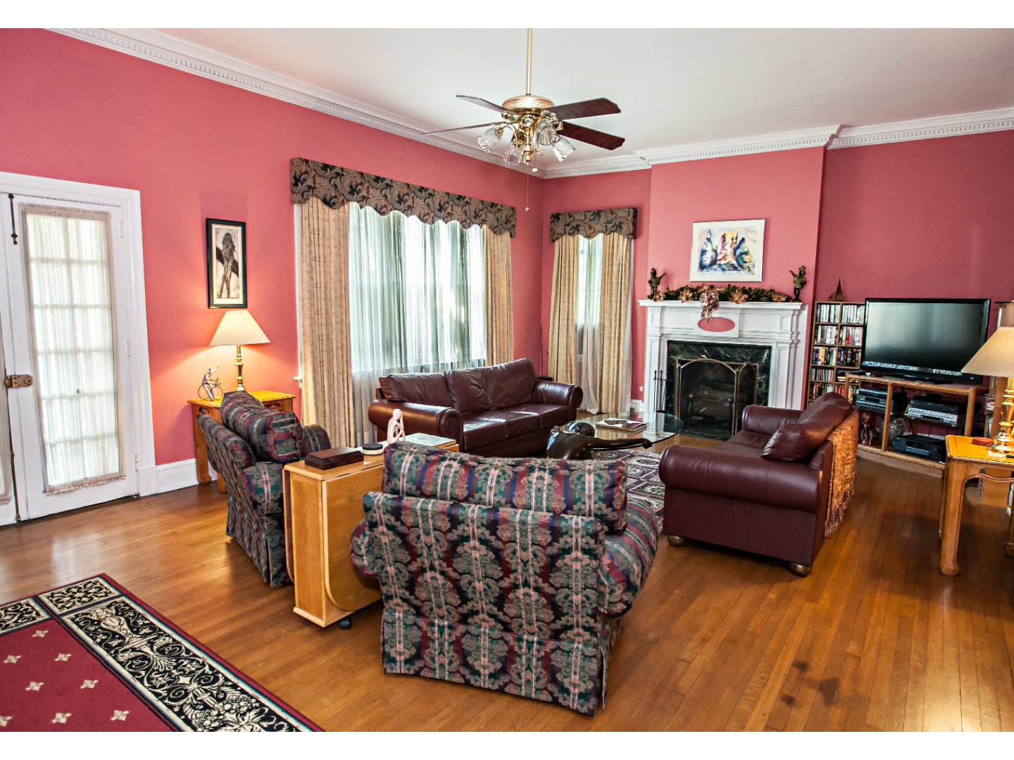 A living room filled with furniture and a fireplace at Morehead Manor Bed and Breakfast.