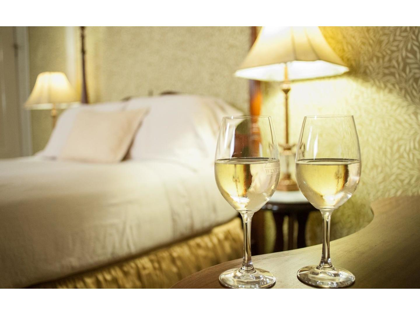 A glass of wine sitting on top of a bed at Camellia Inn.