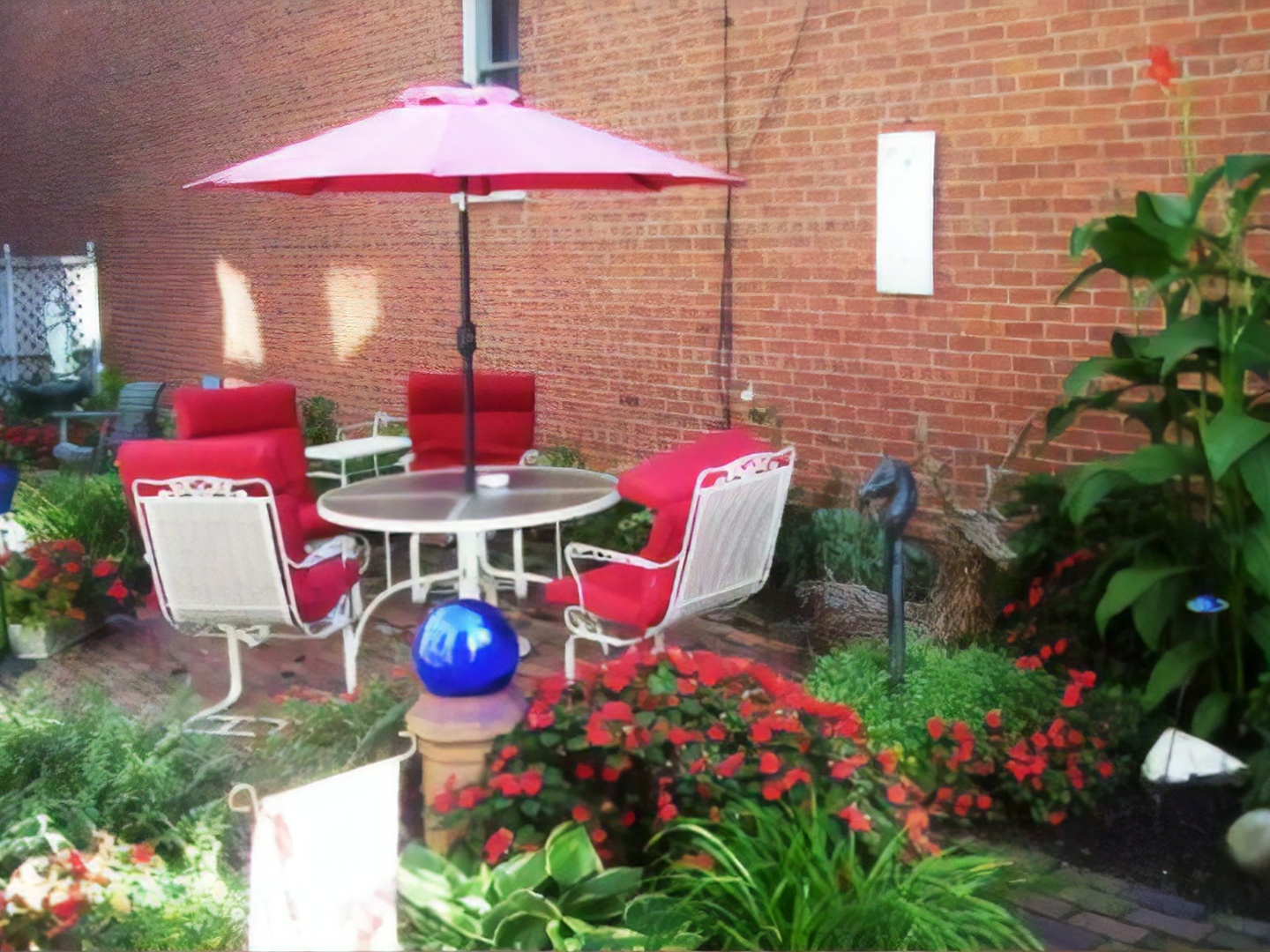 A large red chair in a garden at Gateway Bed and Breakfast.