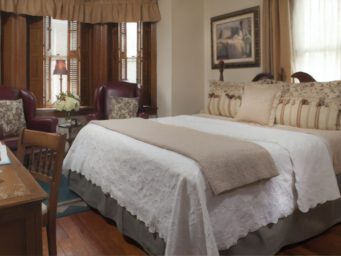 A bedroom with a bed and desk in a hotel room at Harvest Moon Bed & Breakfast.