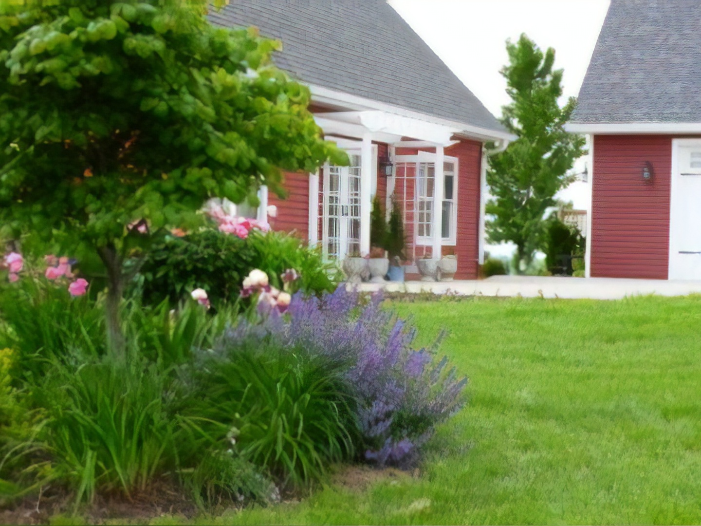 A close up of a flower garden in front of a house at Longview Farms Bed & Breakfast Carriage House.