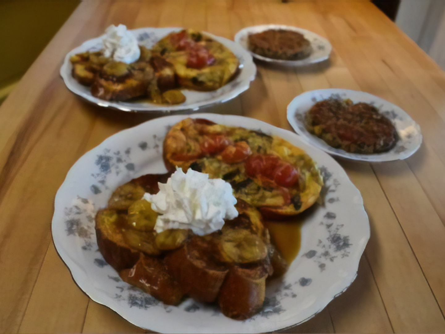 A wooden table topped with plates of food on a plate at Apple Bin Inn Bed and Breakfast.