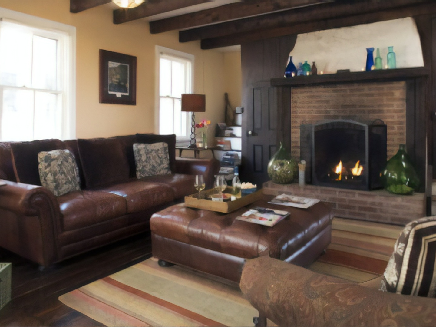 A brown leather couch in a living room filled with furniture and a fireplace at Pheasant Field Bed and Breakfast.