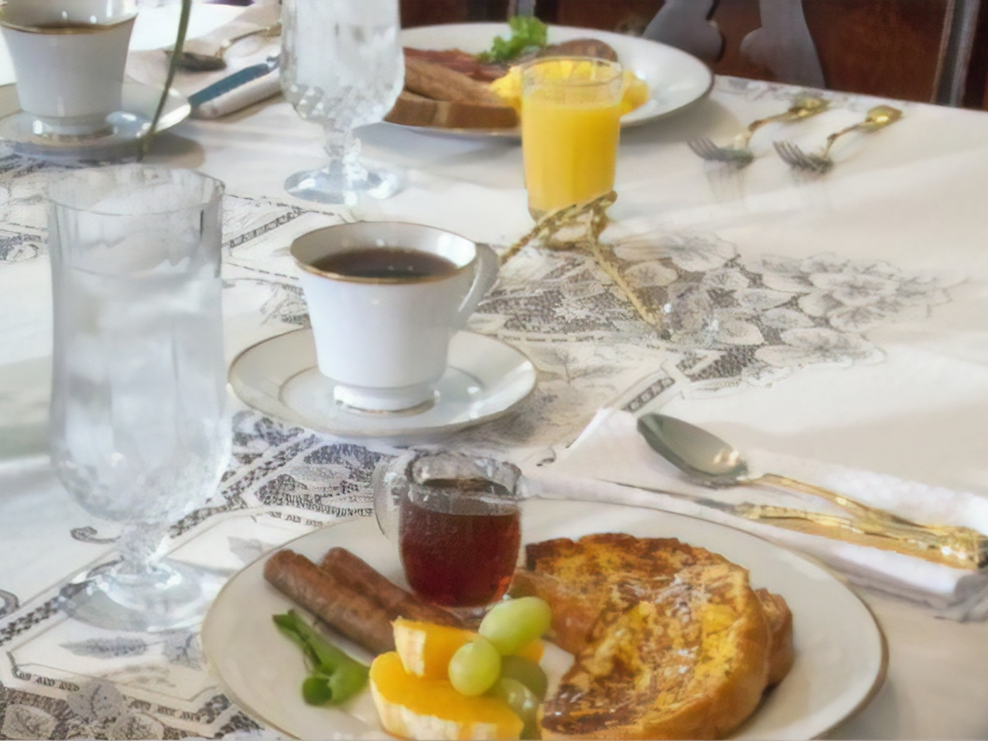 A plate of food and a cup of coffee on a table at Gateway Bed and Breakfast.