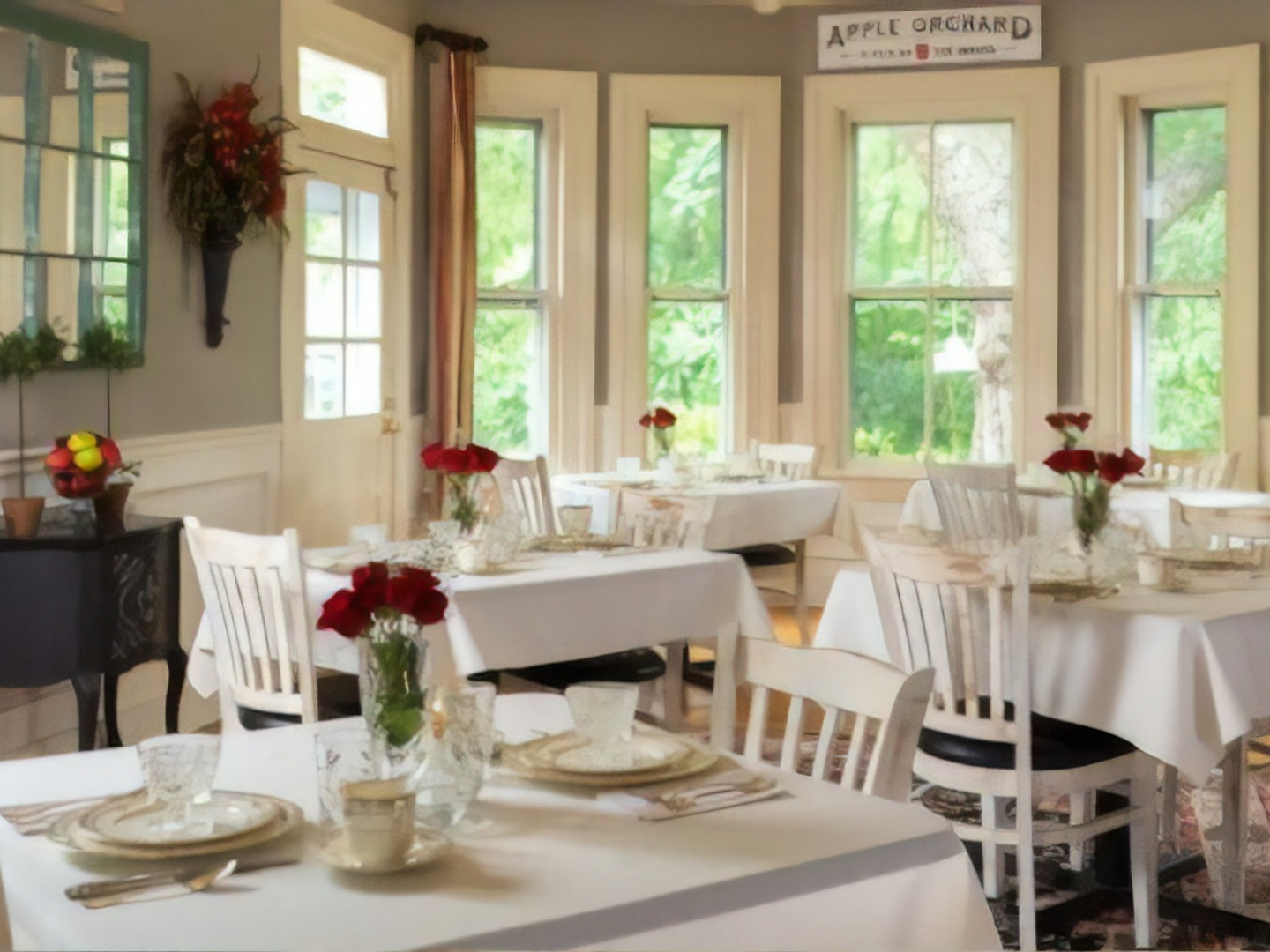 A dining room table in front of a window at Orchard House Bed & Breakfast.