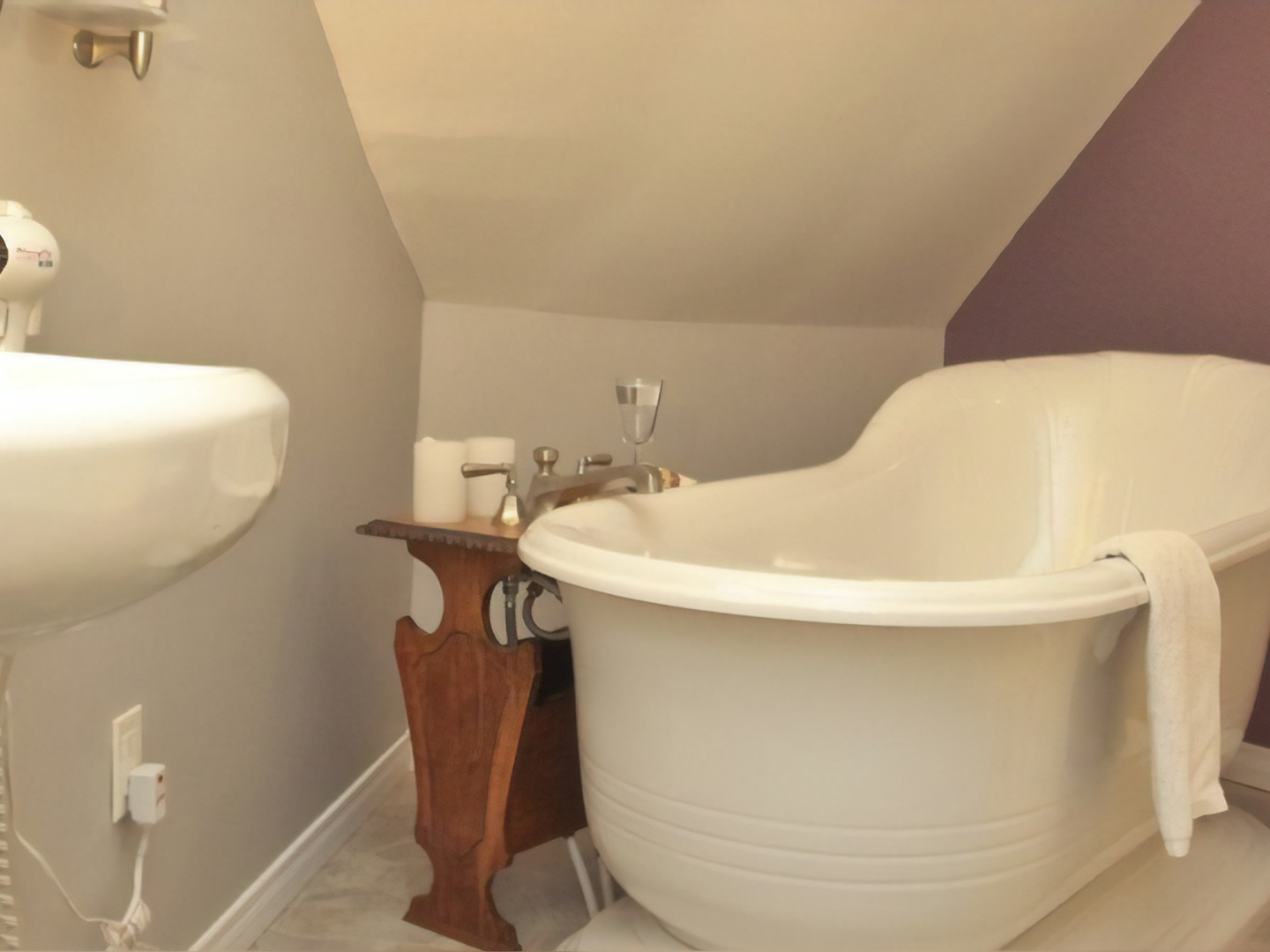 A large white tub sitting next to a sink at Sleepy Hollow Bed & Breakfast.