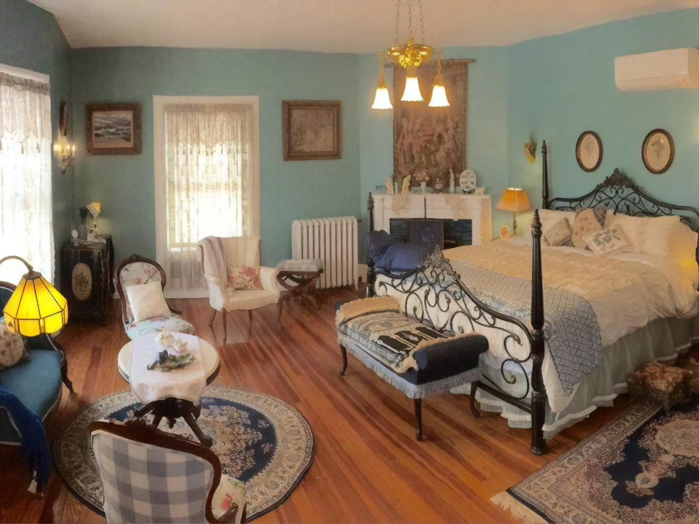 A bedroom with a fireplace in a living room at Berkeley House Bed & Breakfast.