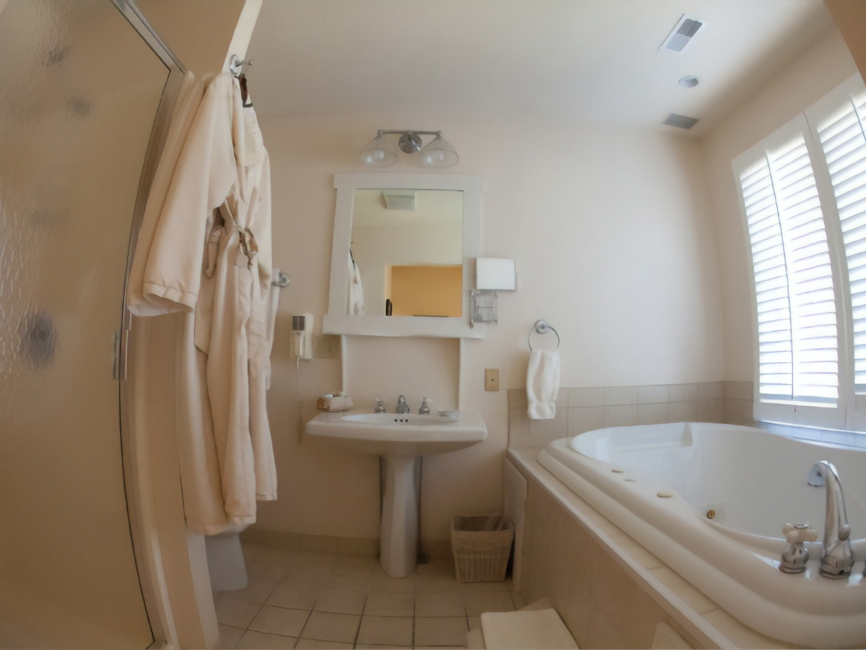 A large white tub sitting next to a sink at Glenlaurel, A Scottish Inn & Cottages.