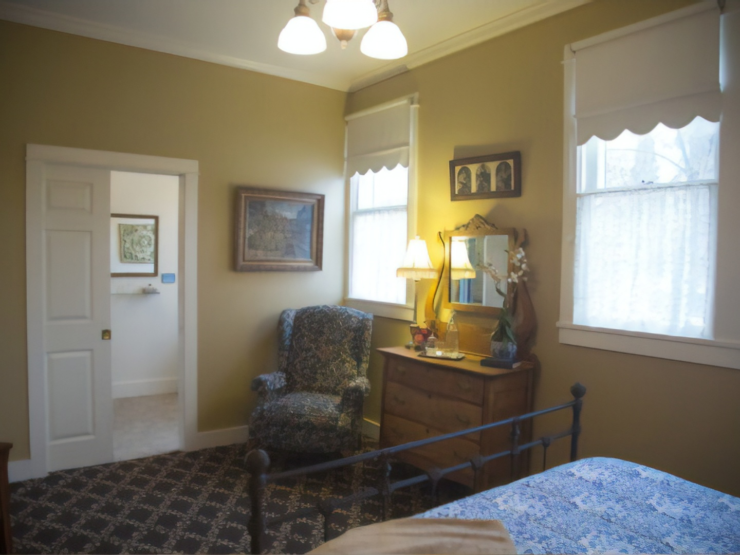 A bedroom with a large window at Jacksonville's Magnolia Inn.