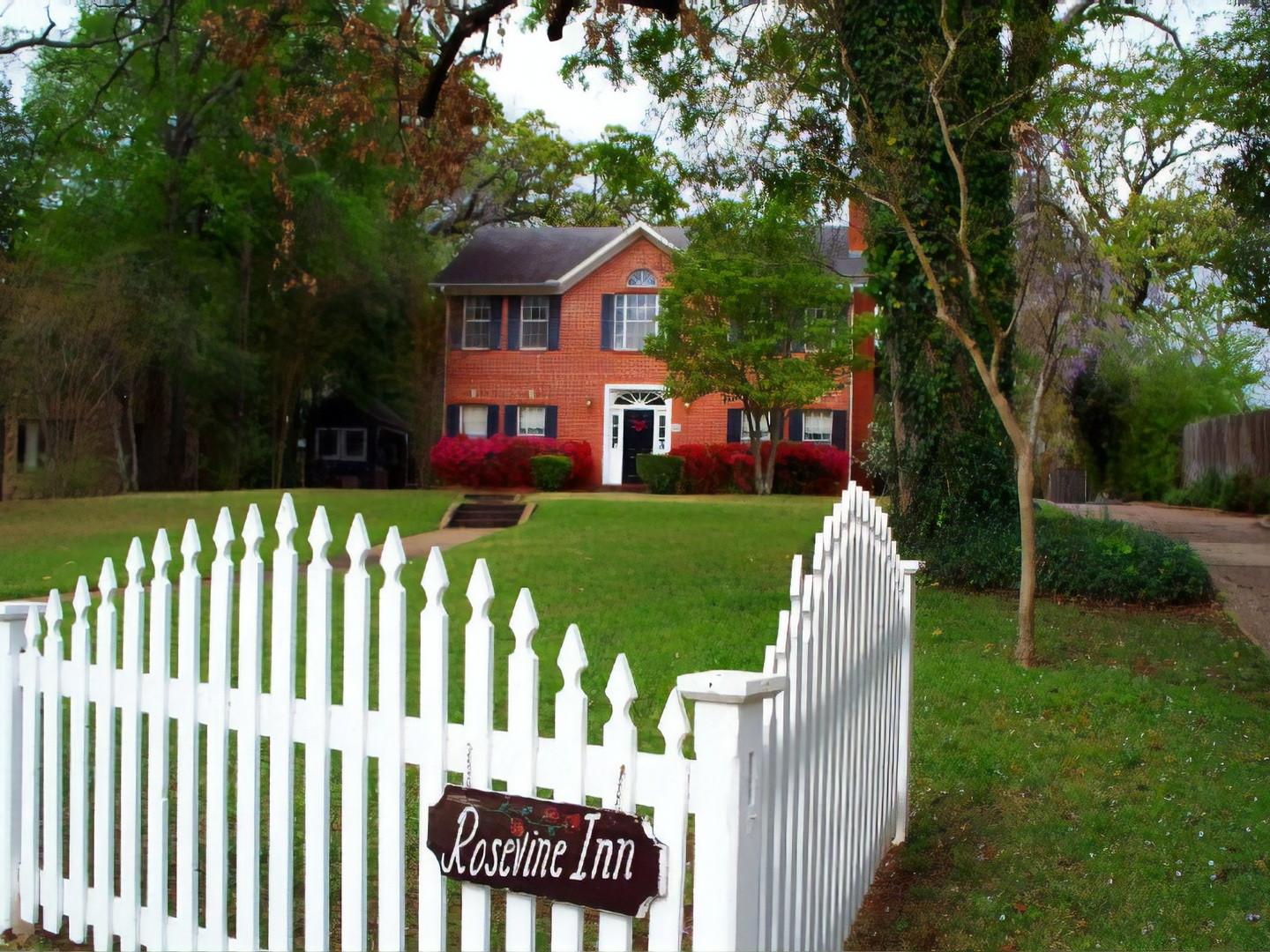 A white park bench sitting in front of a fence at Rosevine Inn Bed & Breakfast and Extended Stay Lodging.