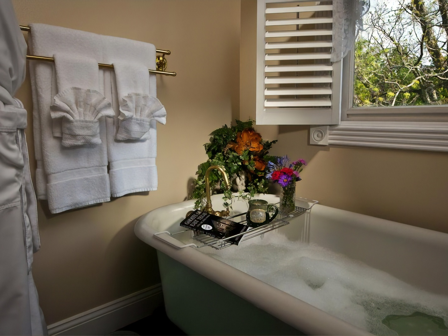 A large white tub sitting next to a window at White Oak Manor Bed and Breakfast.