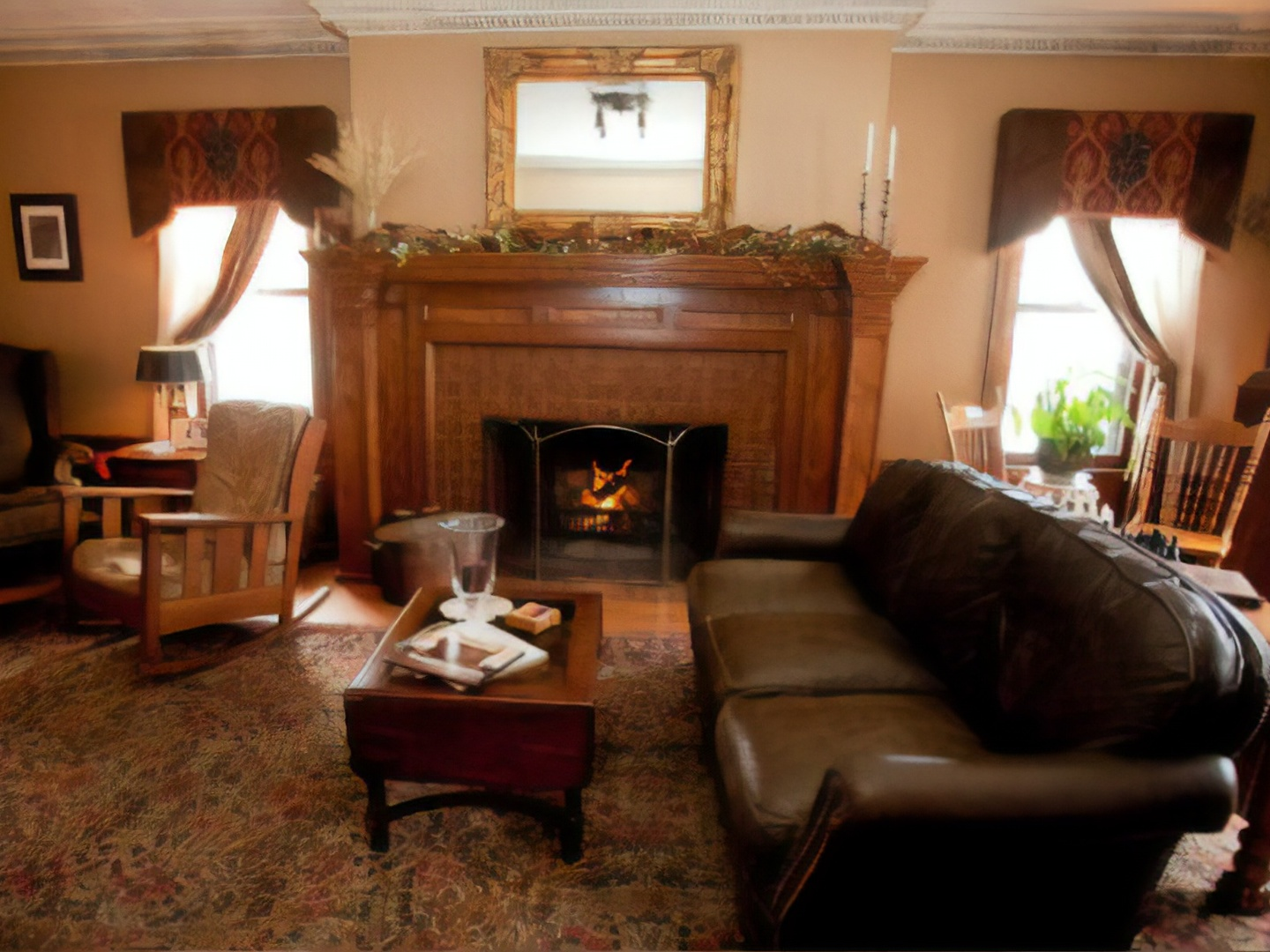 A living room filled with furniture and a fire place at Westphal Mansion Inn Bed and Breakfast.