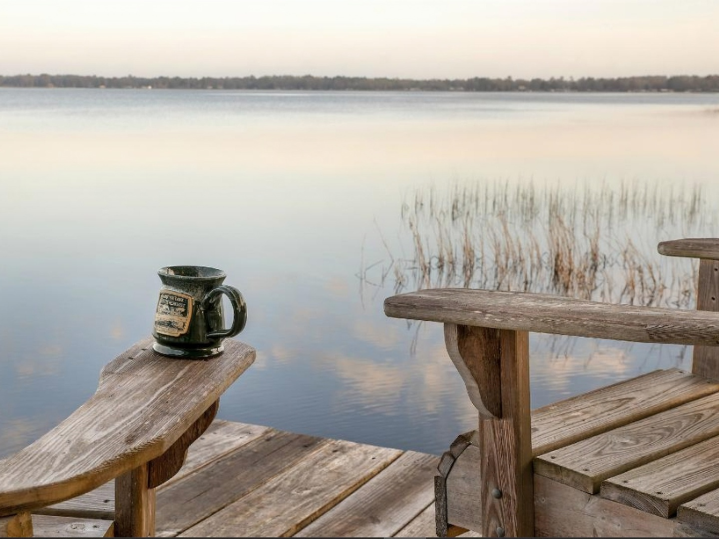 A wooden bench next to a body of water at Hampton Lake Bed & Breakfast.