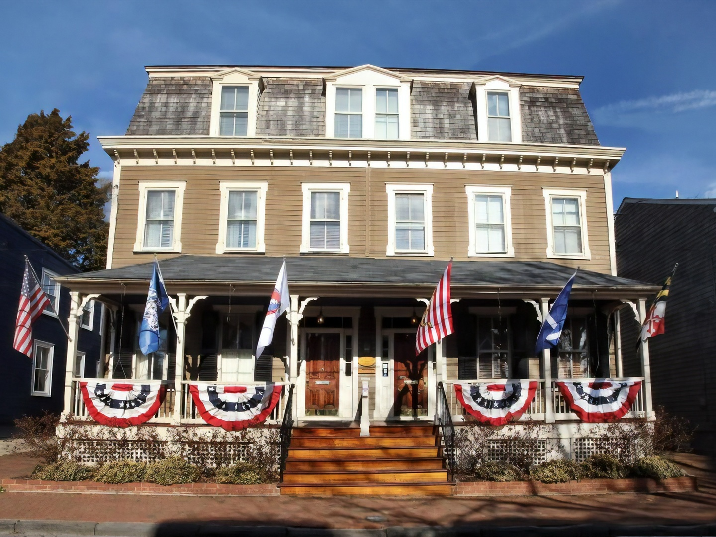 A group of people in front of a building at Flag House Inn.