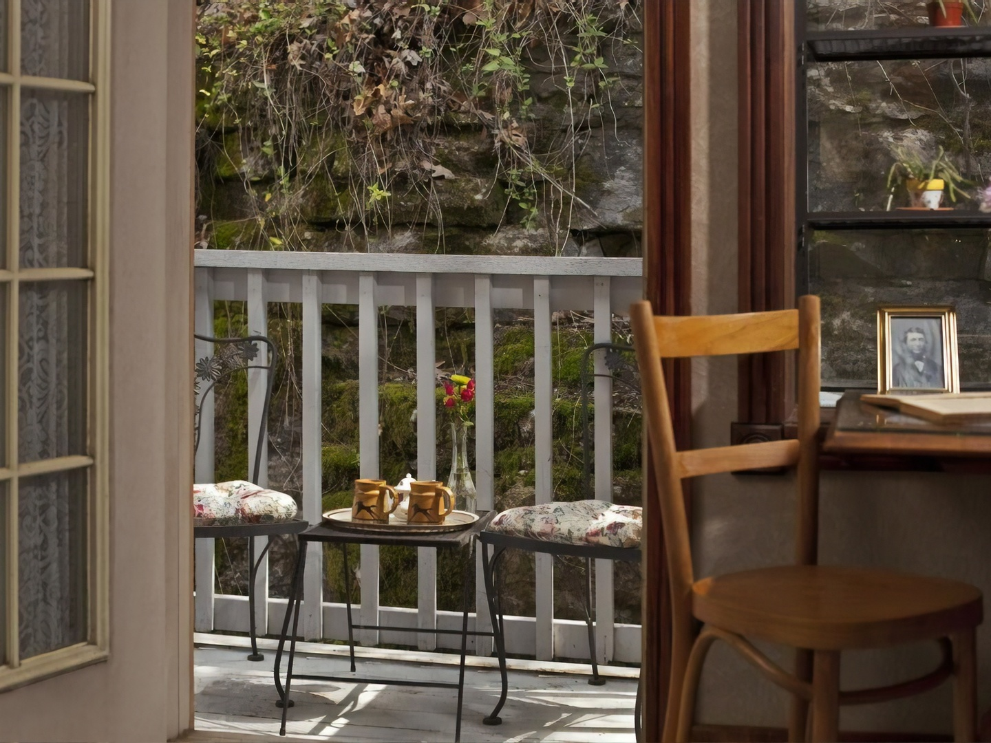 A dining room table in front of a window at Cliff Cottage Inn - Boutique Hotel and Bed & Breakfast.