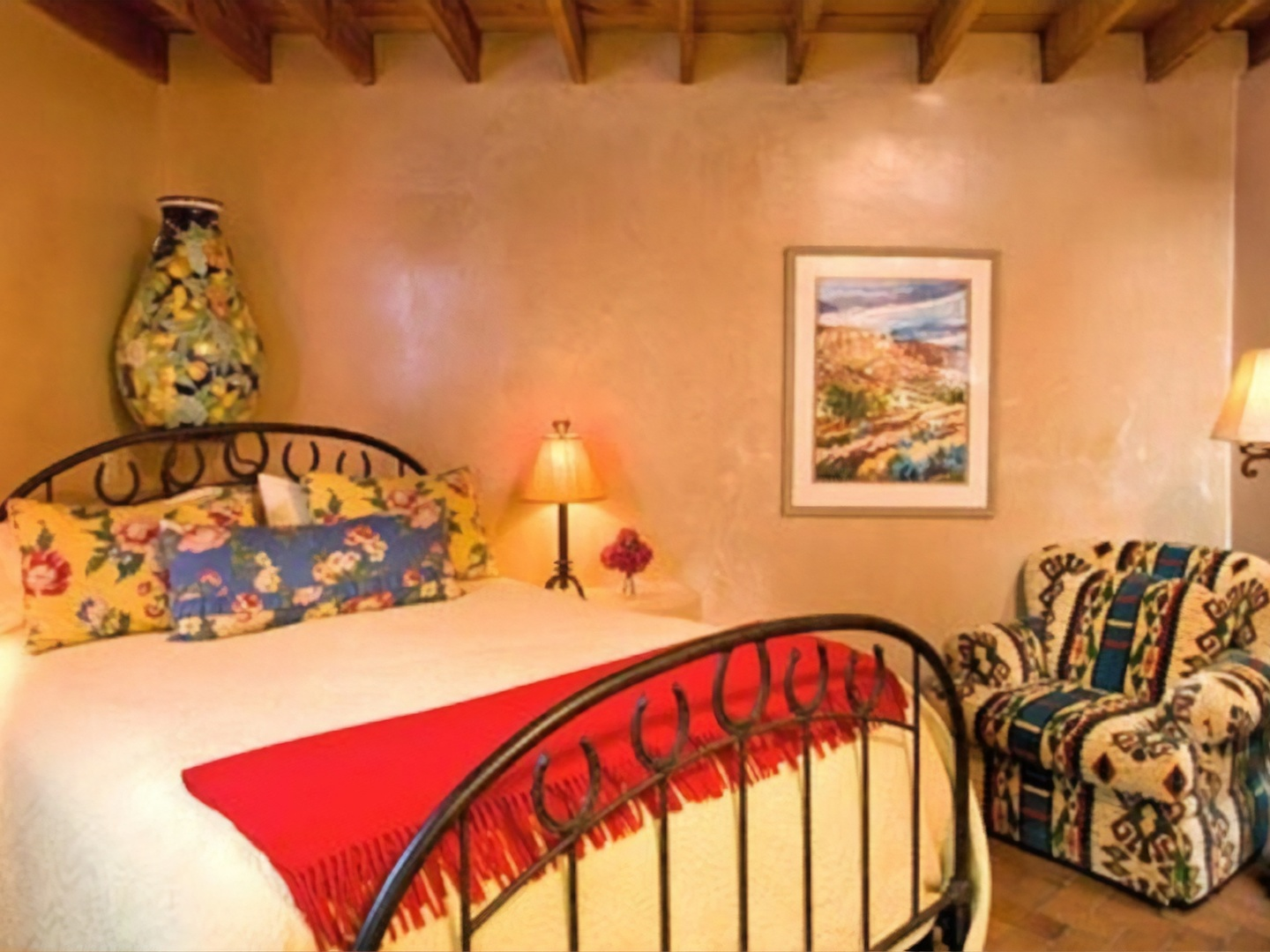A bedroom with a bed and a painting on the wall at El Farolito Bed & Breakfast.