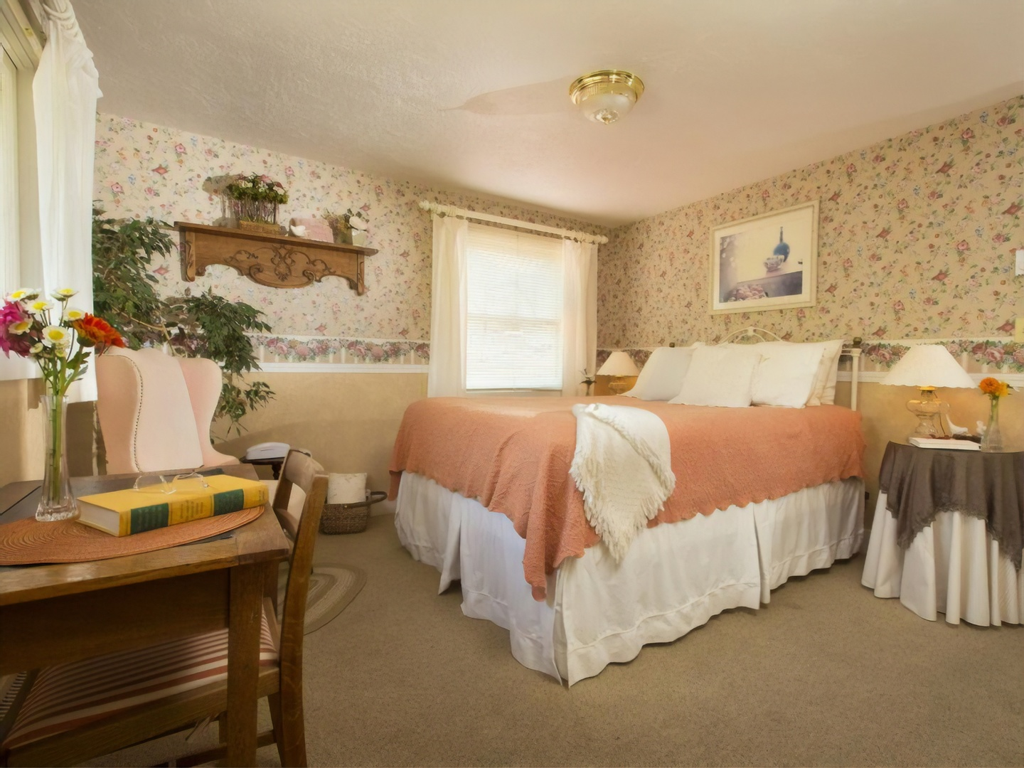 A bedroom with a bed and desk in a room at Country Willows Inn & Estate.