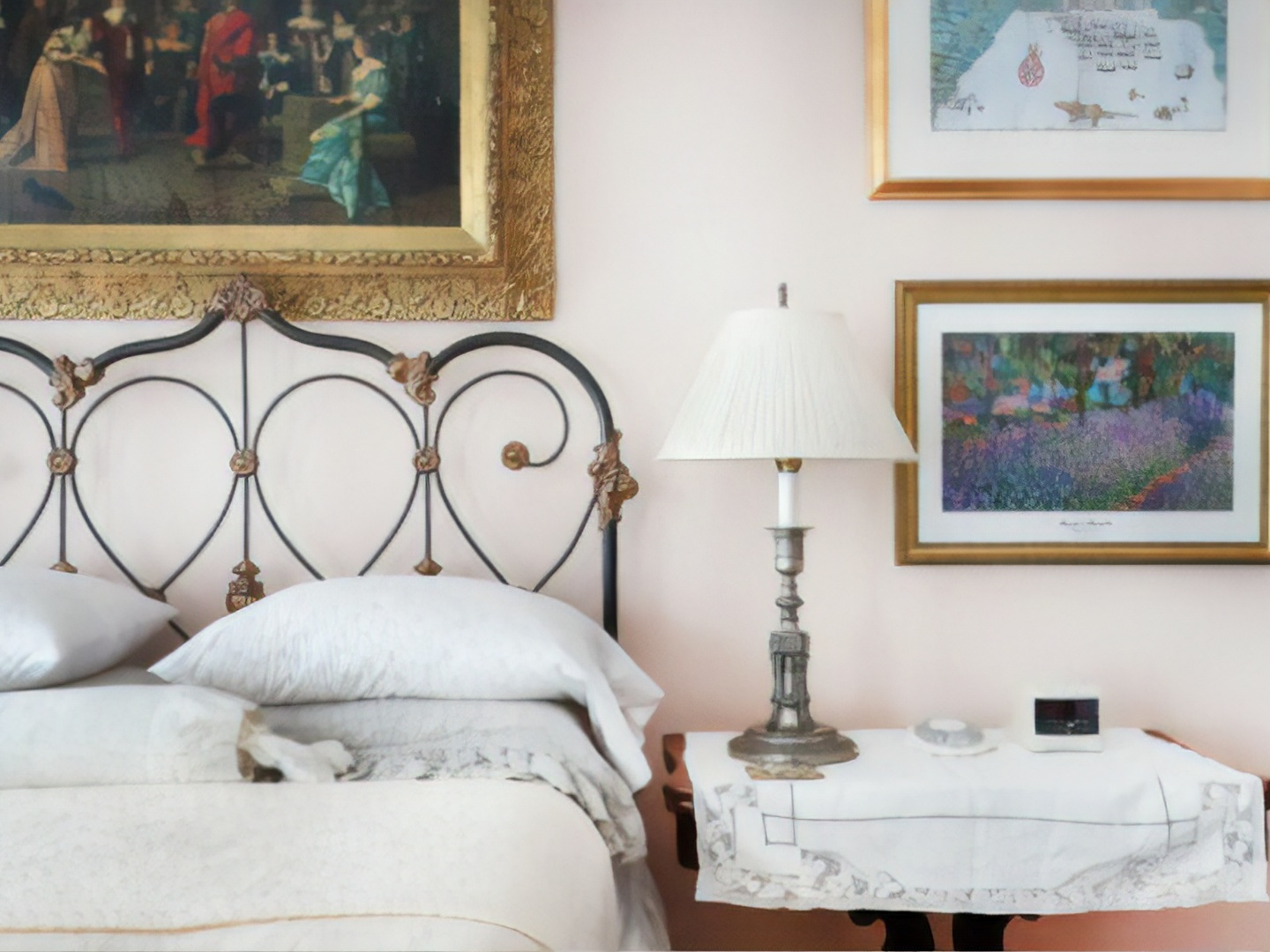 A bedroom with a bed and a painting on the wall at 1871 House.