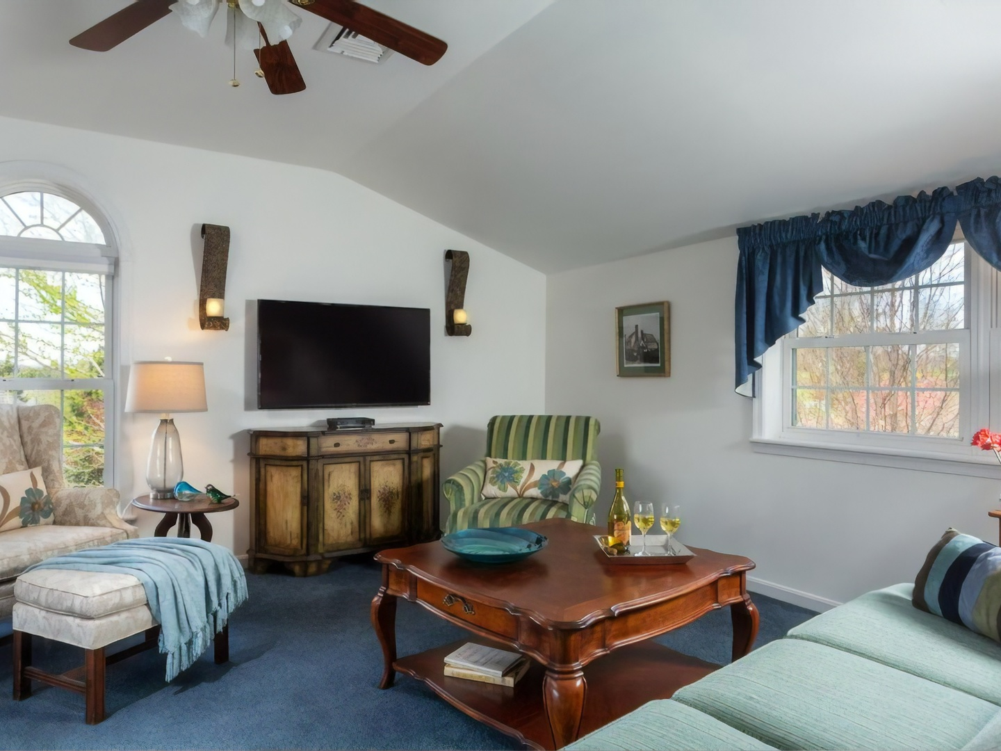 A living room filled with furniture and a large window at The Inn at Westwynd Farm.