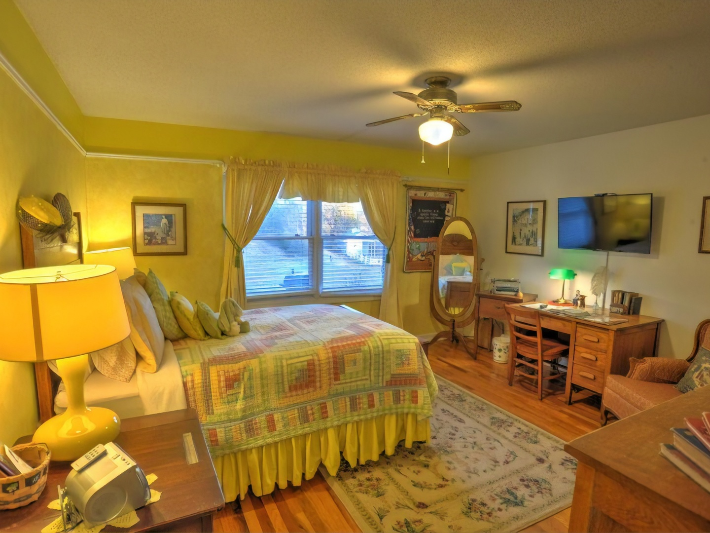 A bedroom with a bed and desk in a room at Blue Mountain Mist Country Inn and Cottages.