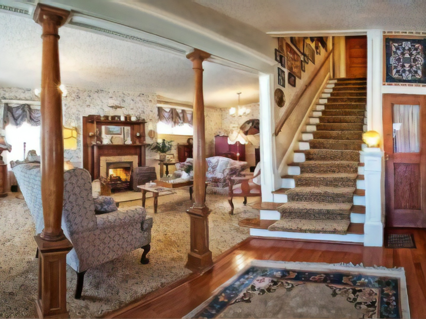 A living room filled with furniture and a fireplace at Holden House 1902 Bed & Breakfast Inn.