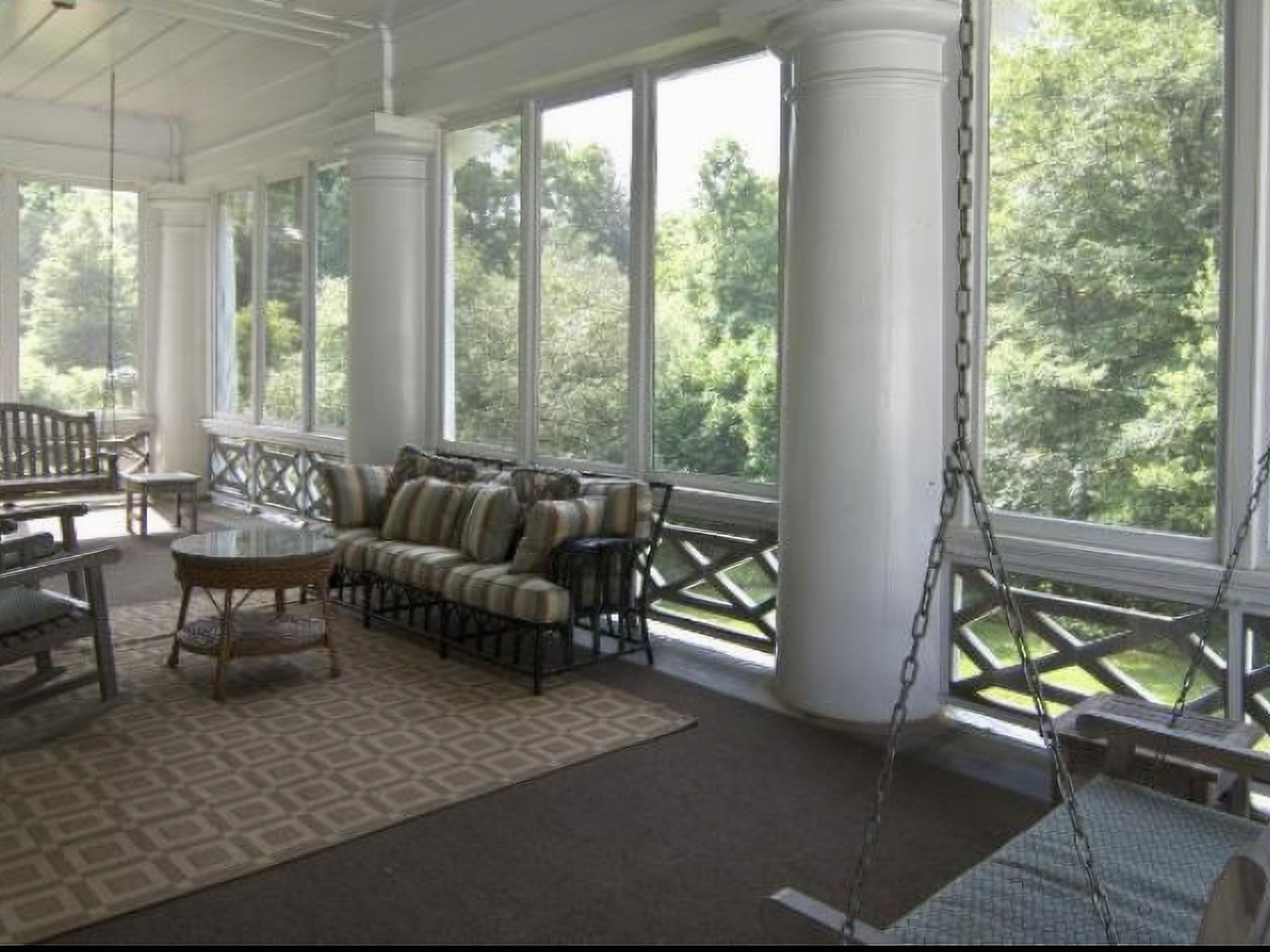 A living room filled with furniture and a large window at The Duke Mansion.