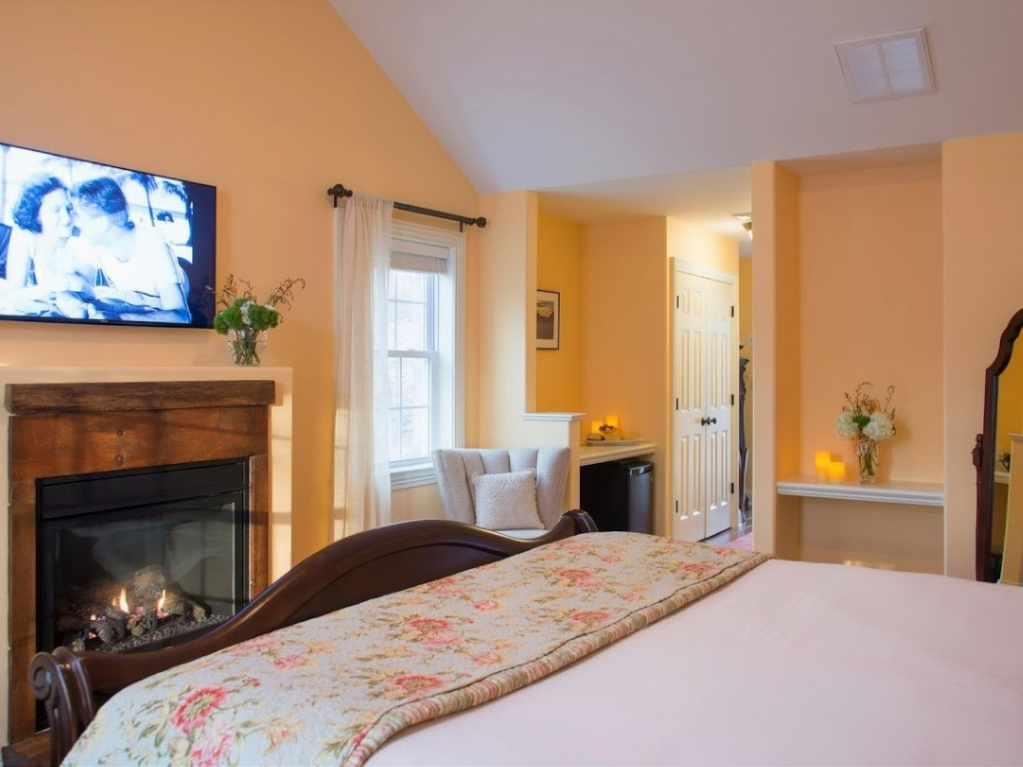 A living room with a flat screen tv sitting on top of a bed at Caldwell House Bed & Breakfast.