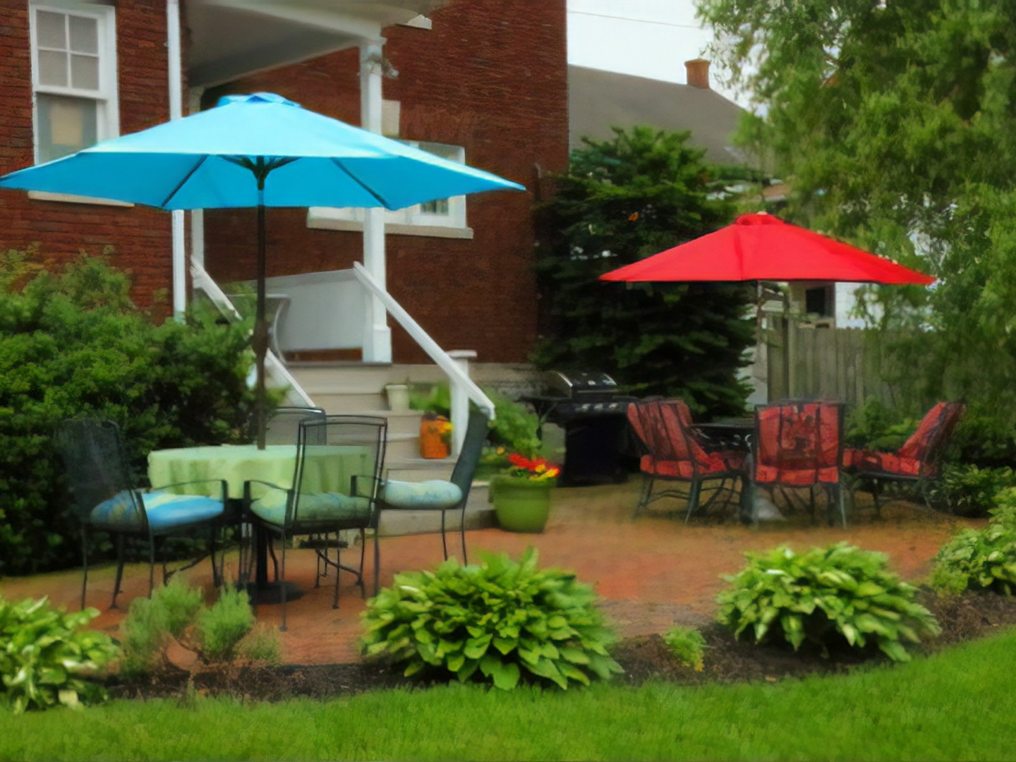 A group of lawn chairs sitting on top of a green umbrella at Olde Square Inn.