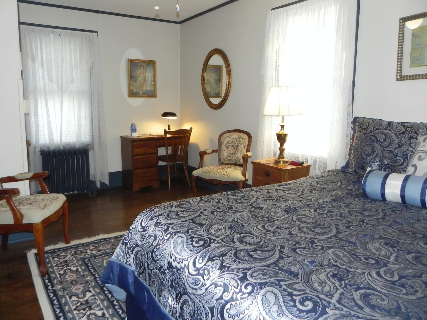 A bedroom with a bed and desk in a room at Vine Cottage Inn.