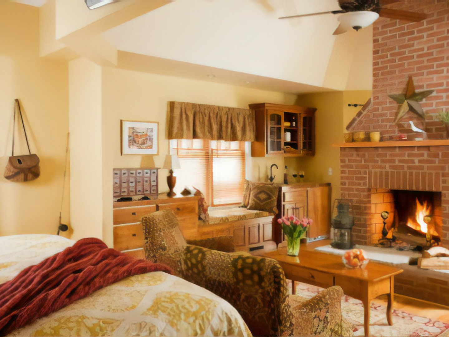 A living room with a bed and a fireplace at Brampton Bed and Breakfast Inn.