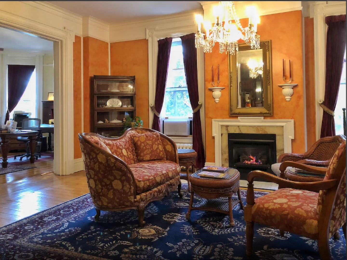 A living room filled with furniture and a fireplace at Willard Street Inn.