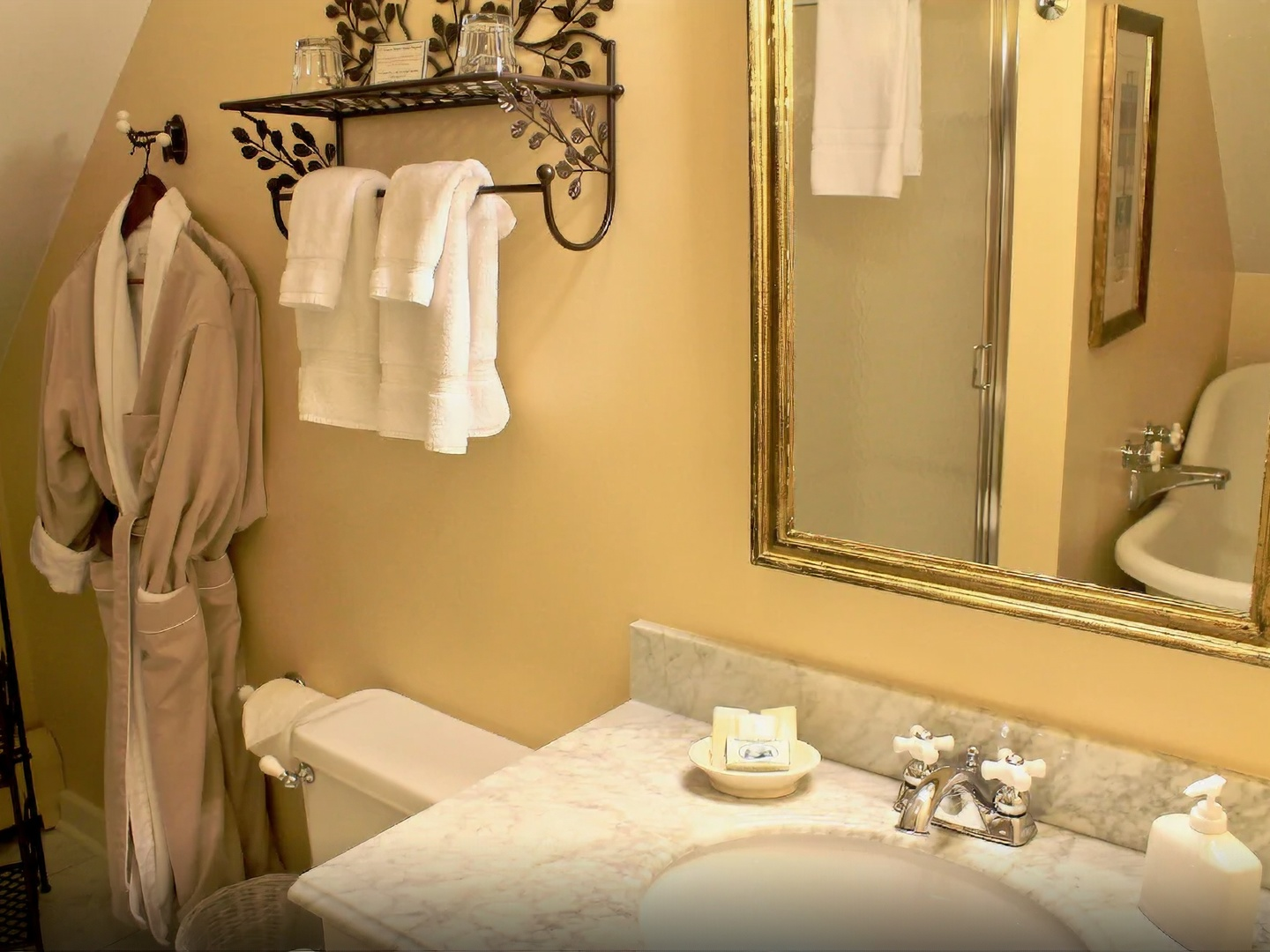 A hotel room with a sink and a mirror at Willard Street Inn.