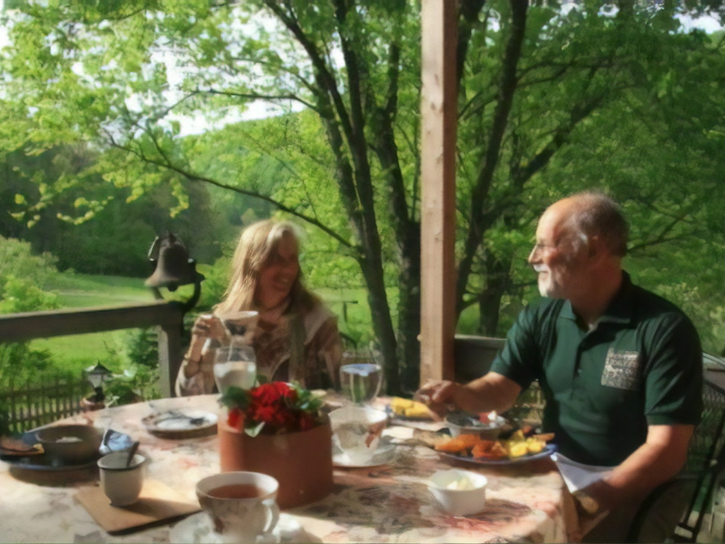 A group of people sitting at a table eating food at Snug Hollow Farm Bed and Breakfast.