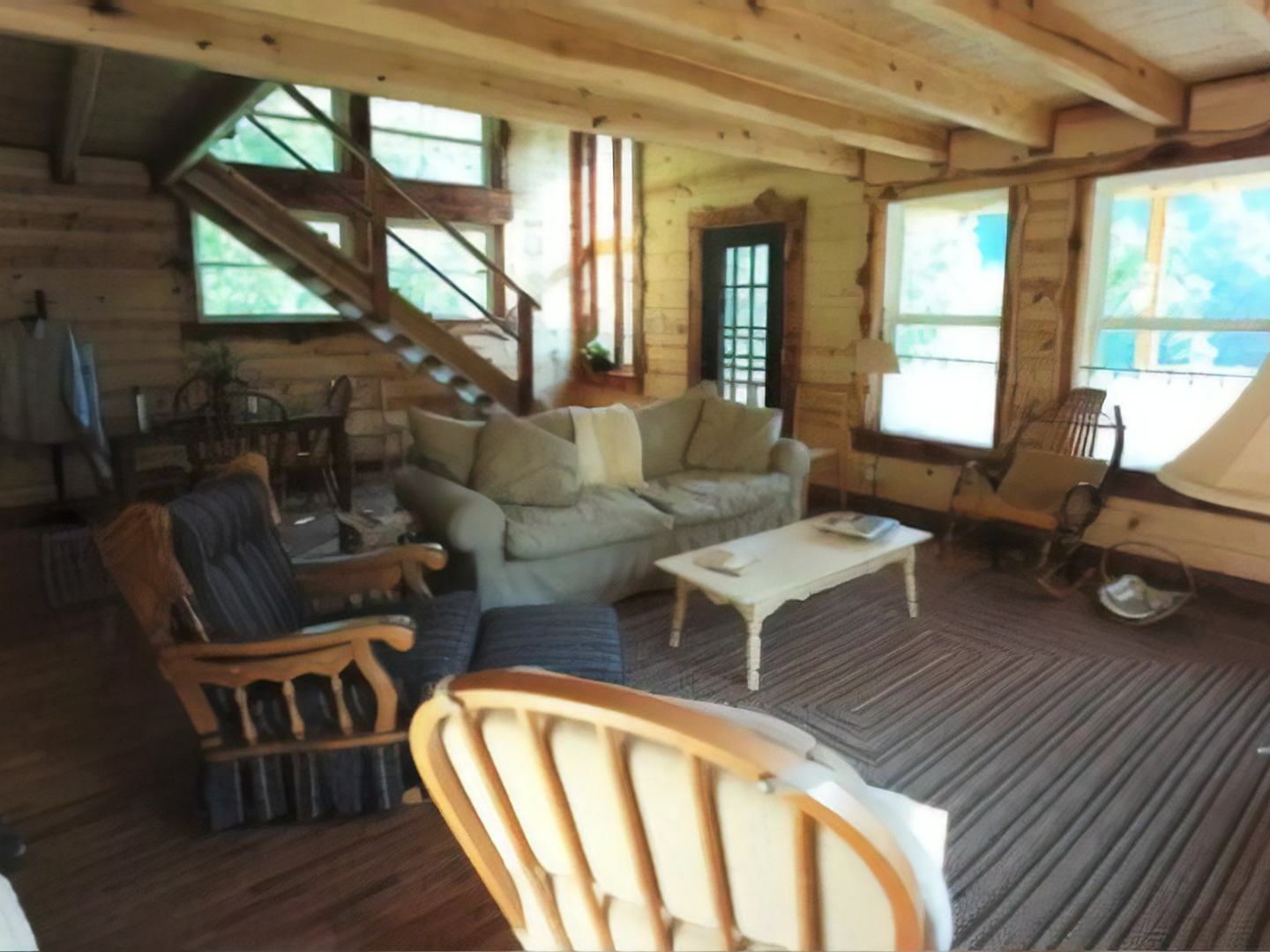 A living room filled with furniture and a large window at Snug Hollow Farm Bed and Breakfast.