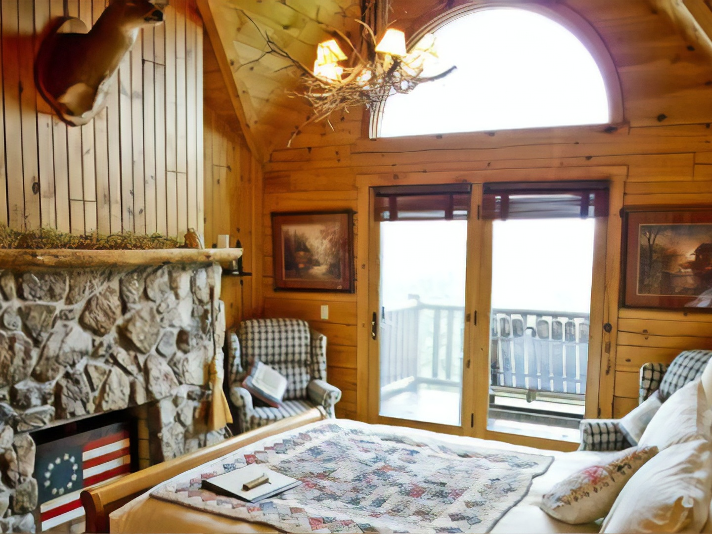 A bedroom with a fireplace and a large window at North Fork Mountain Inn Bed & Breakfast.
