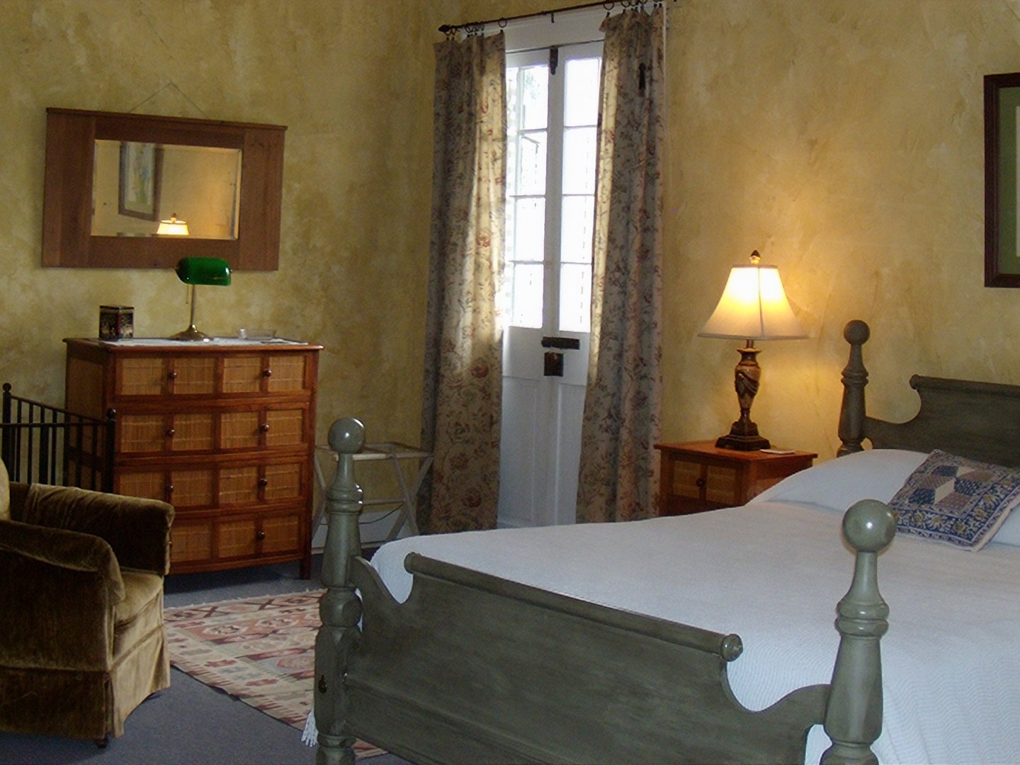 A bedroom with a bed and a mirror in a room at Pierre Coulon Guest House.