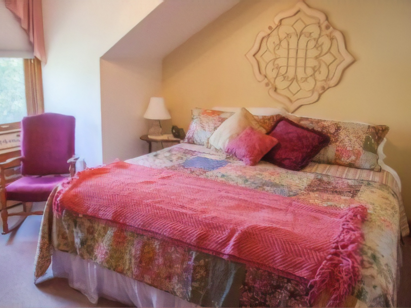 A bed with a pink blanket at Bross Hotel Bed & Breakfast.