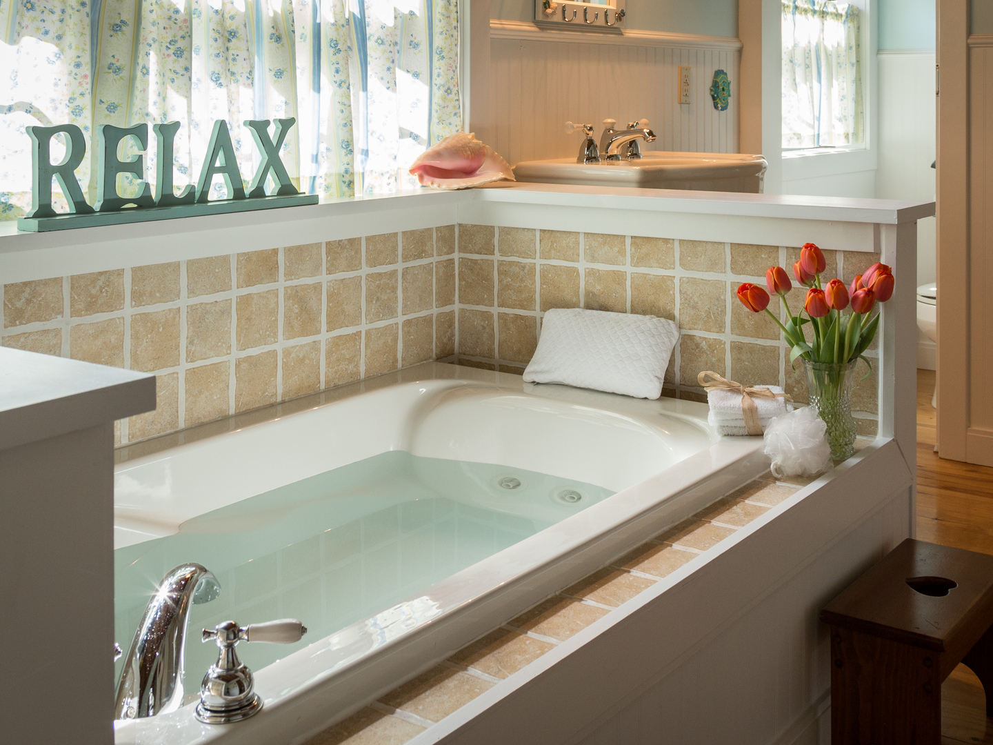 A white tub sitting next to a sink at Tiffany's Bed and Breakfast.