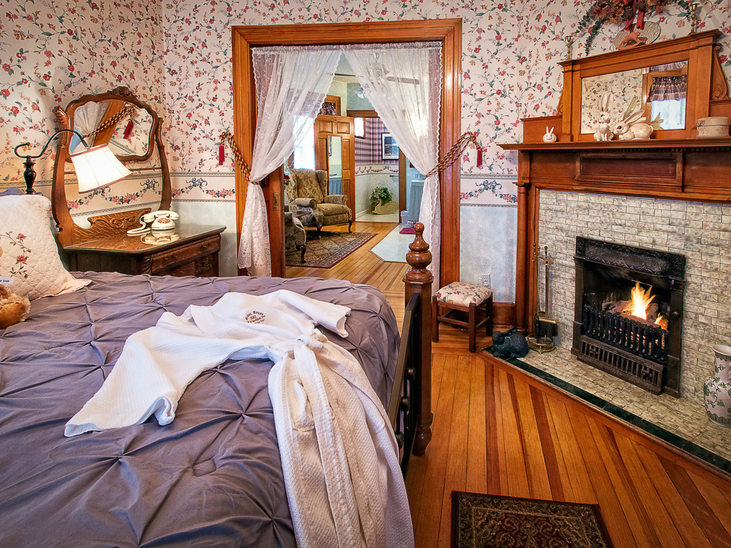 A bedroom with a bed and a fireplace at Holden House 1902 Bed & Breakfast Inn.