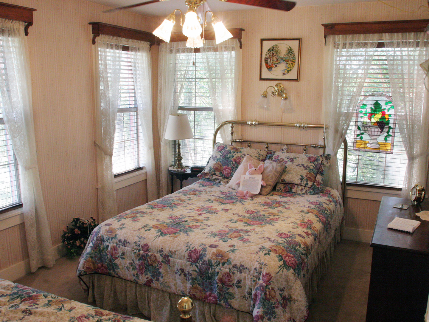 A bedroom with a bed and desk in a room at Rosevine Inn Bed & Breakfast and Extended Stay Lodging.