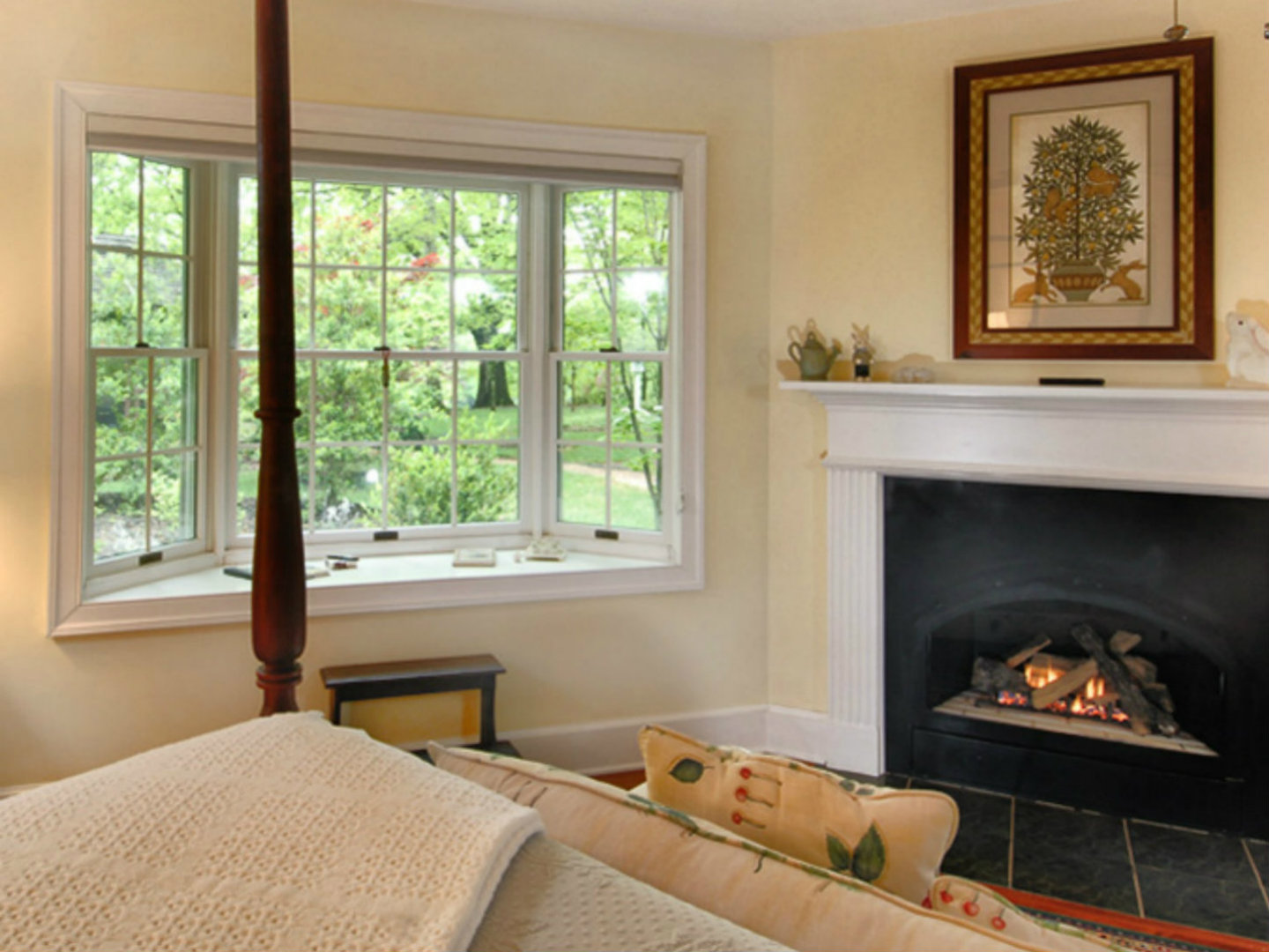 A living room with a fireplace and a large window at Foxfield Inn.