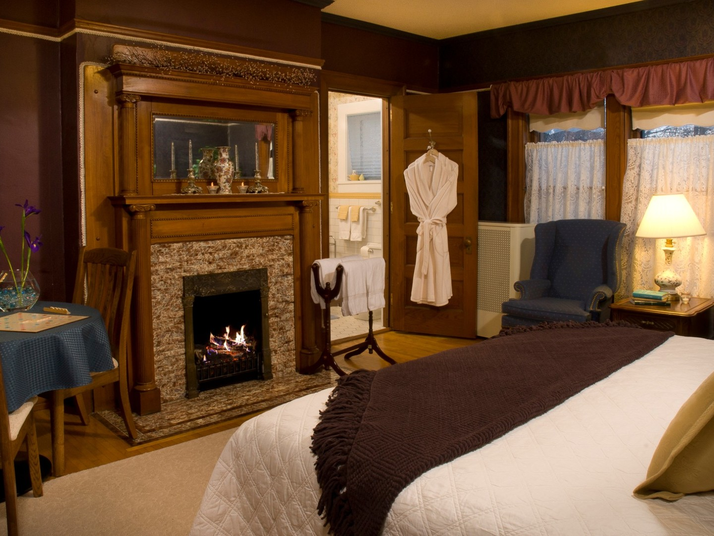 A bedroom with a bed and a fireplace at Franklin Victorian Bed and Breakfast.