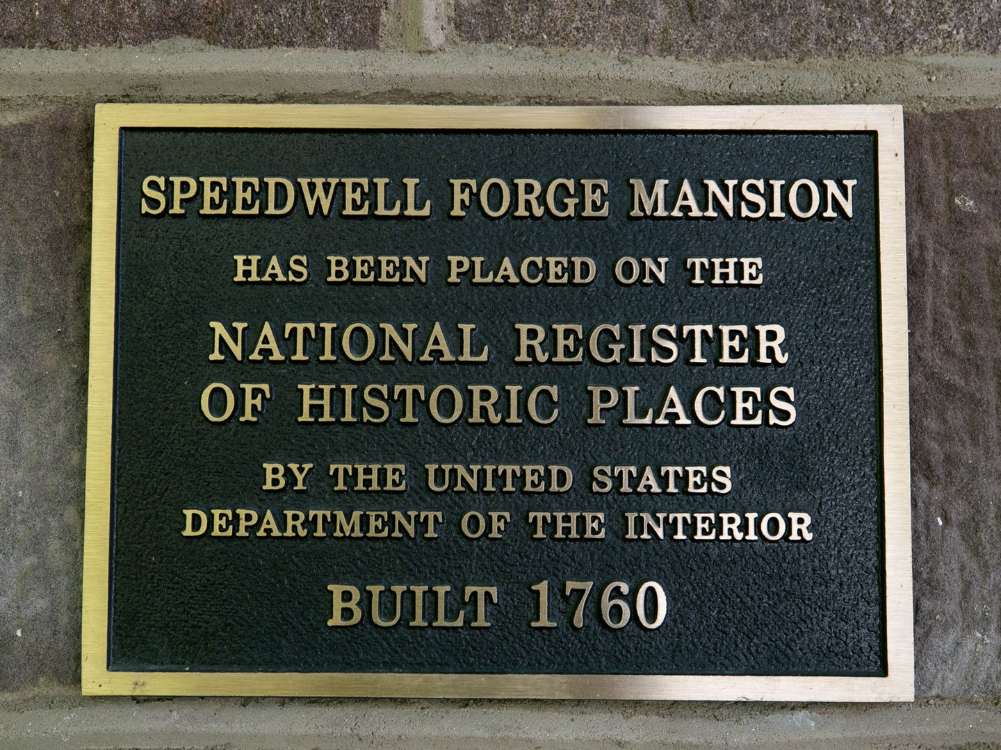 A plaque in front of a sign at Speedwell Forge B&B.