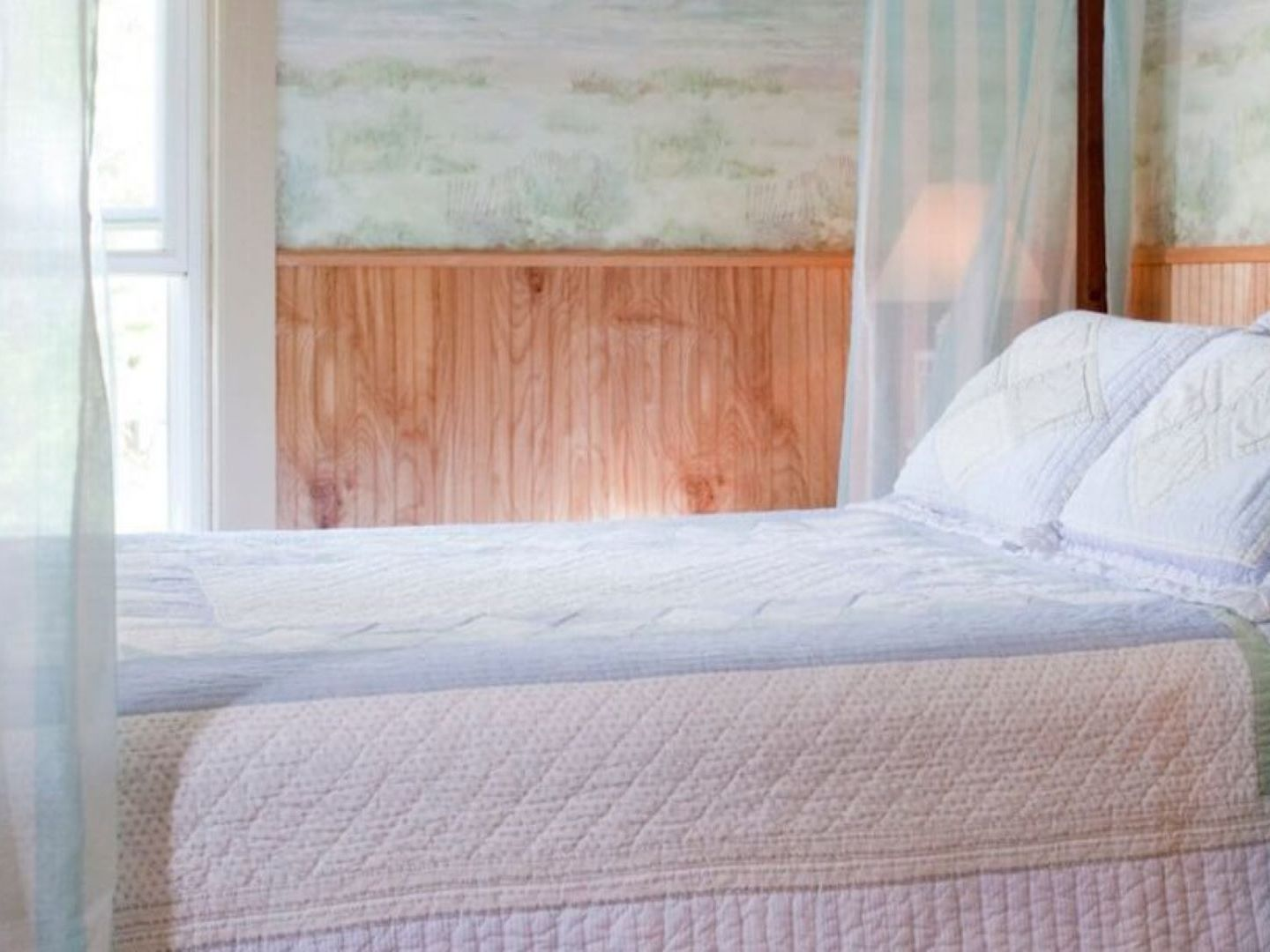 A made bed in a bedroom next to a window at Blueberry Cove Inn.