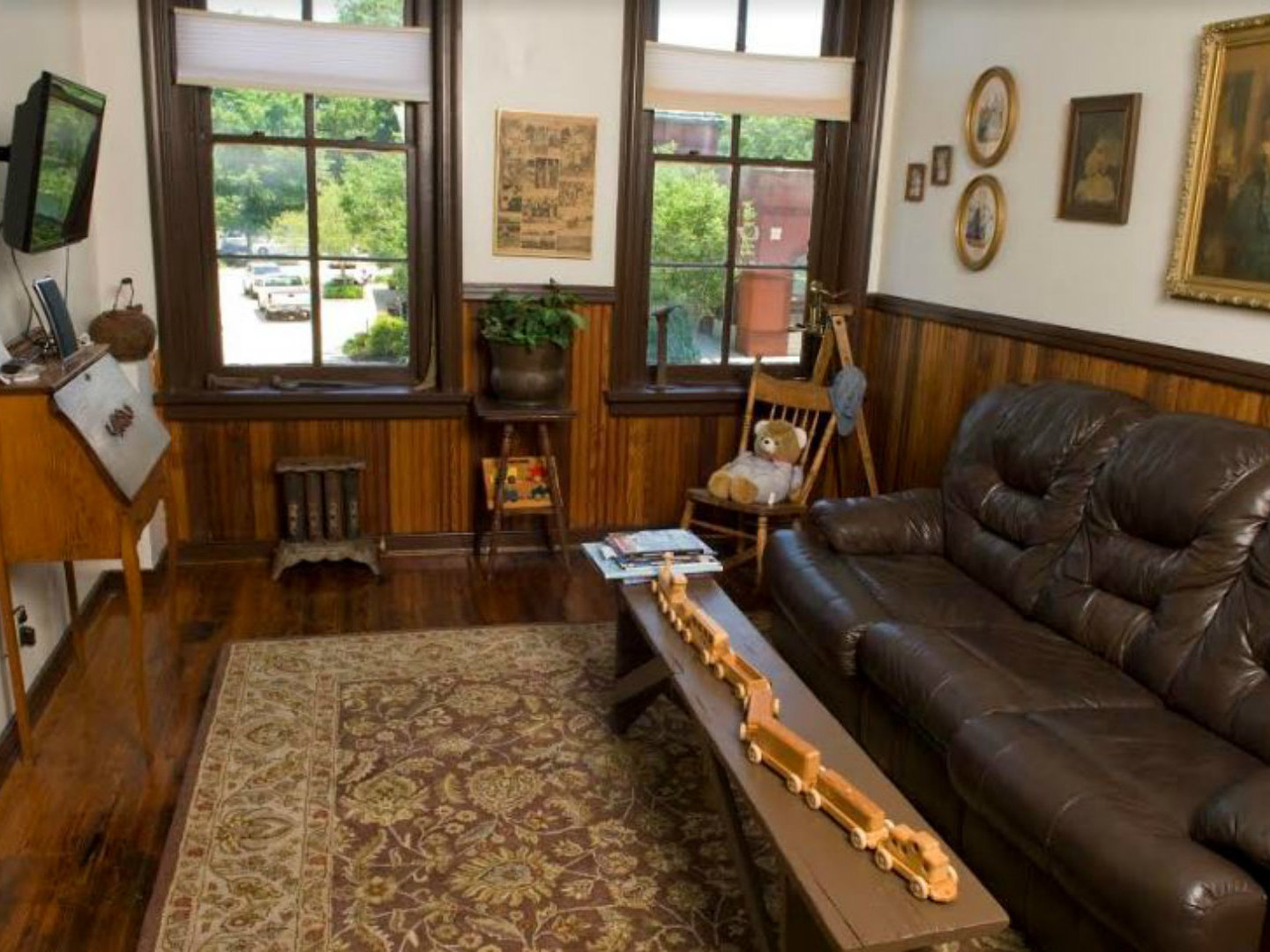 A living room filled with furniture and a large window at Tinder Guest House.