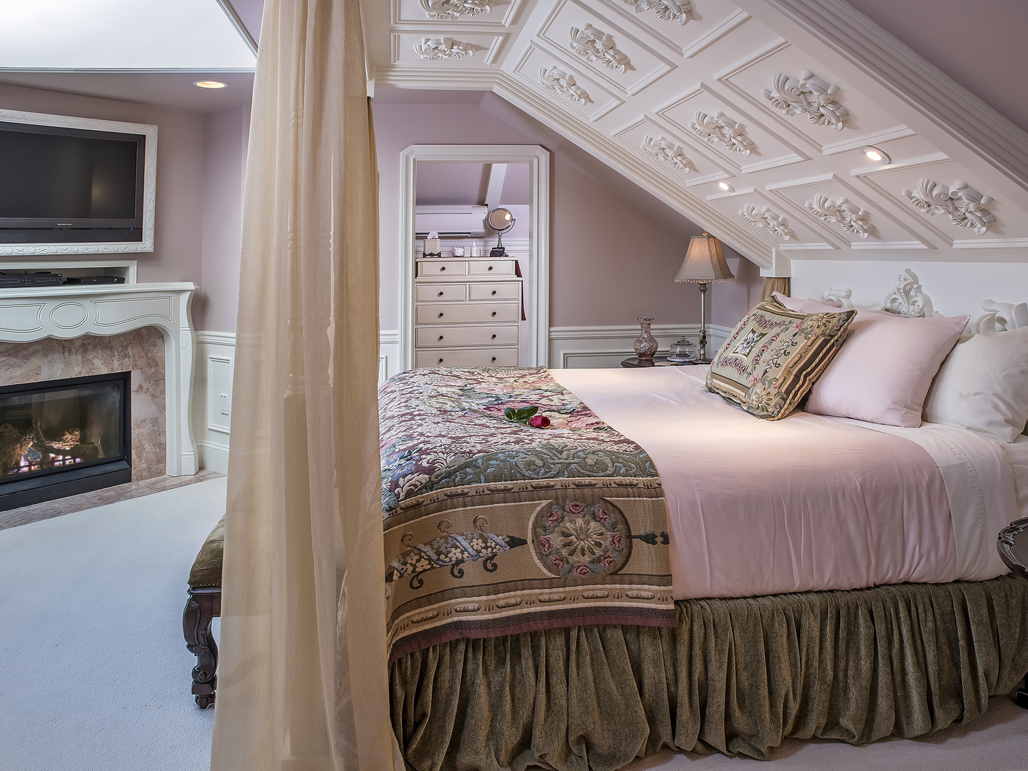 A bedroom with a bed and a fireplace at Cameo Heights Mansion.