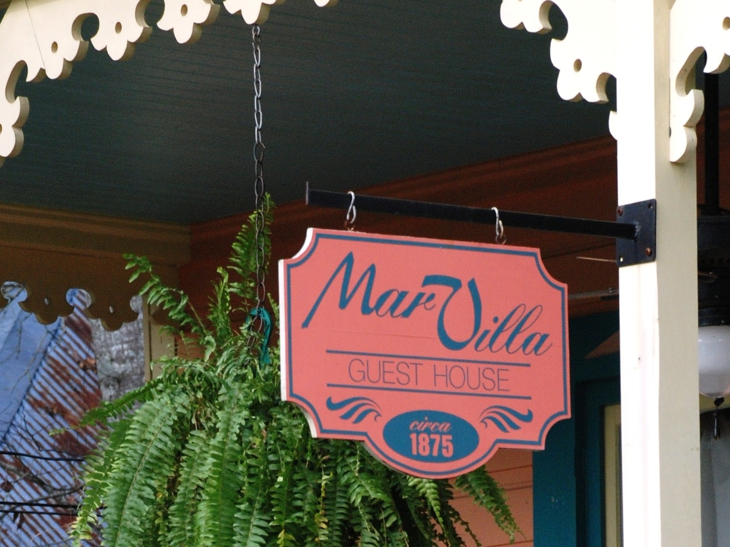 A sign hanging off the side of a building at Marvilla Guest House.